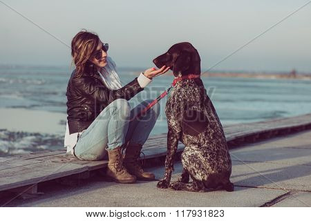 Young woman train her German pointer dog outdoor