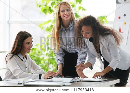 Three young businesswomen at the meeting in a conference room