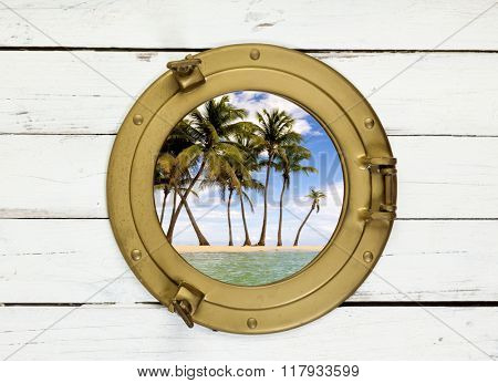 Palm trees on tropical island seen through vintage brass porthole in wooden wall