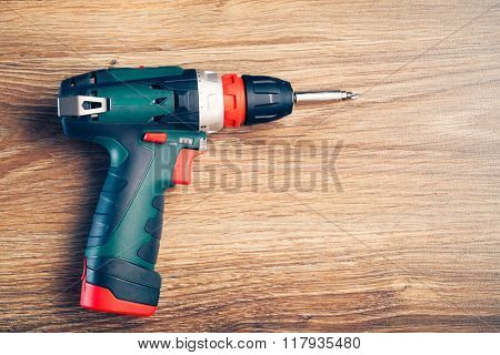 electric screwdriver on wooden background