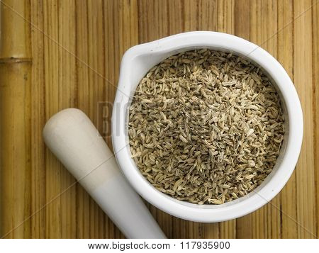 cumin seeds in mortar on the bamboo background