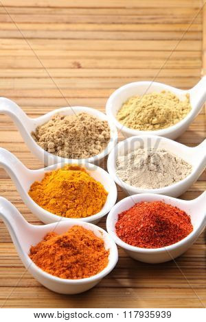 assorted curry powder in saucers on the bamboo background