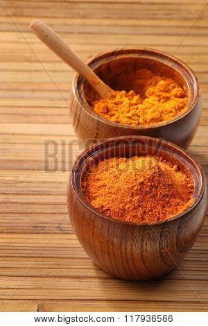 chili powder in a wooden bowl on the bamboo background