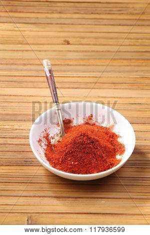 chili powder in a saucer on the bamboo background