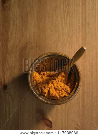 curry powder in a bowl on the wooden background