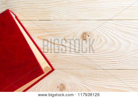 Red book on wooden table. Top View. Back to school. Copy space
