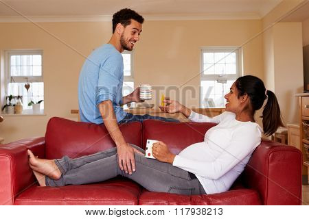 Pregnant Woman Relaxes On Sofa With Husband