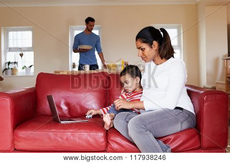 Pregnant Mother Looks At Laptop On Sofa With Son