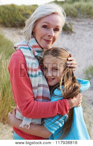 Grandmother With Granddaughter Standing On Beach