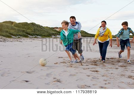 Parents Playing Soccer With Children On Beach