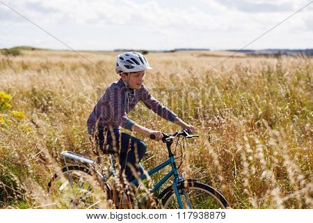 Boy Riding Bike Through Countryside