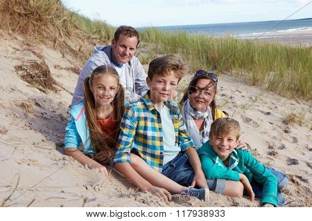 Portrait Of Parents With Children Sitting On Beach