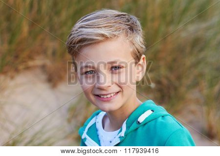 Head And Shoulders Portrait Of Boy By Sand Dunes