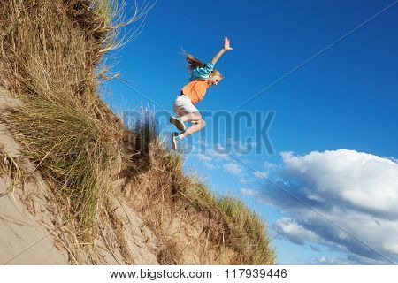 Action Shot Of Girl Jumping From Sand Dune