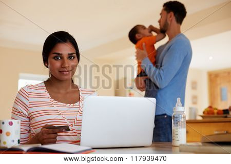 Family In Kitchen With Mother Making On Line Purchase