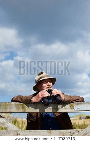 Senior Man With Binoculars Leaning Against Wooden Gate