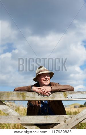 Senior Man On Walk Leaning Against Wooden Gate