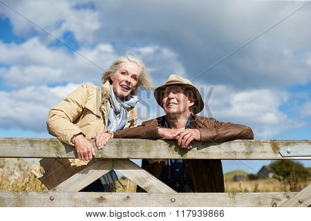Senior Couple On Walk Leaning Against Wooden Gate