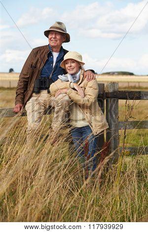 Senior Couple On Walk Leaning Against Wooden Gate