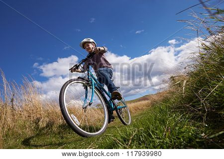Low Angle Shot Of Boy Riding Bike Through Countryside