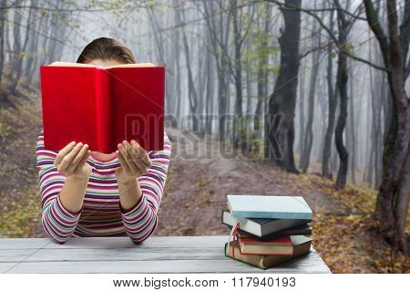 Young woman reading a book and covering her face sitting by wooden table with stack of colorful hardback books on blurred nature landscape backdrop