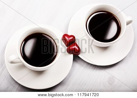 Two cups of coffee and heart shaped sweets