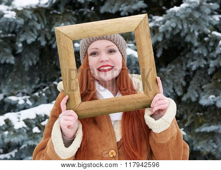 Woman outdoor portrait in wooden photo frame at winter . Snowy weather in fir tree forest.