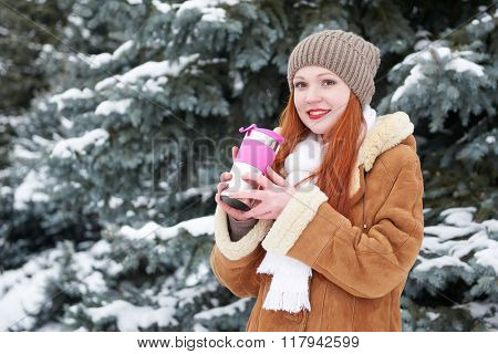 Girl get warm and drink tea in winter forest at day. Fir trees with snow.