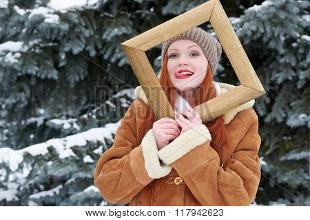 Woman portrait in wooden photo frame at winter season. Snowy weather in fir tree forest.