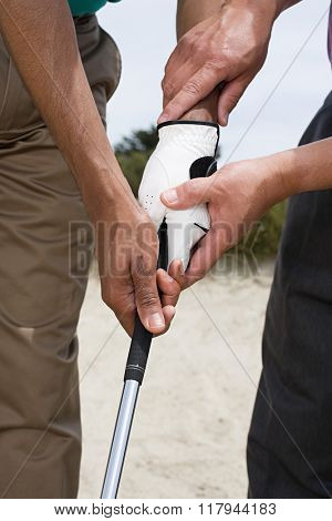 Two people holding a golf club