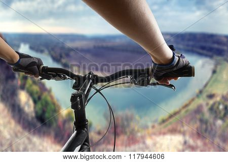 Hands in gloves holding handlebar of a bicycle. Mountain Bike cyclist riding single track. Healthy l