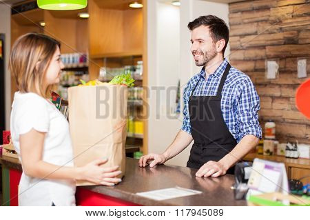 Handsome Cashier Helping Out A Customer