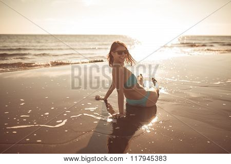 Beautiful brunette woman sitting on sandy beach and smiling, Having fun on holiday vacation