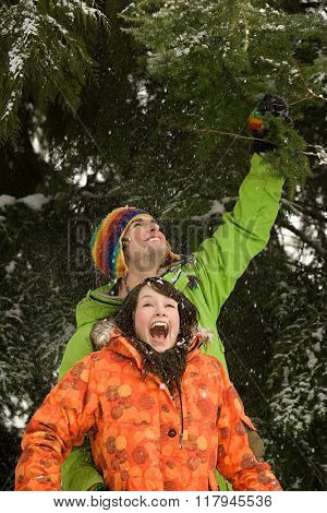 Young couple under snowy tree