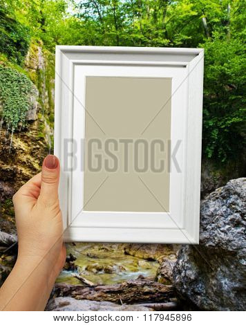 Wooden frame in beautiful woman hands on the background waterfall in forest