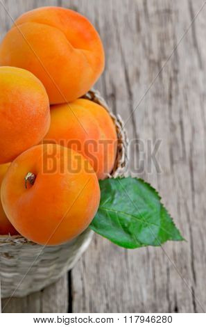 Fresh peaches in the basket on a wooden table