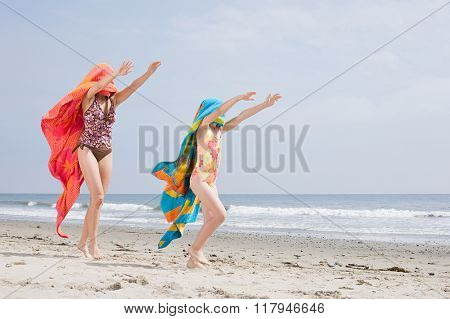 Woman and girl on beach with towels over their heads