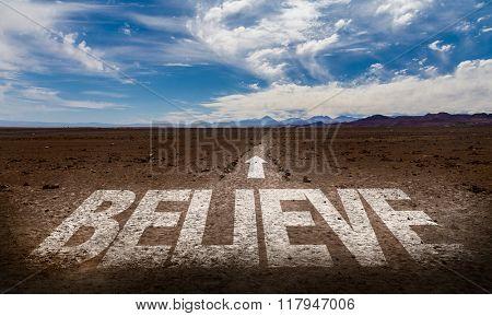 Believe written on desert road