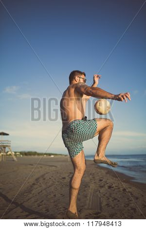 Man playing football on the beach with juggle skill and hitting ball with knee pop