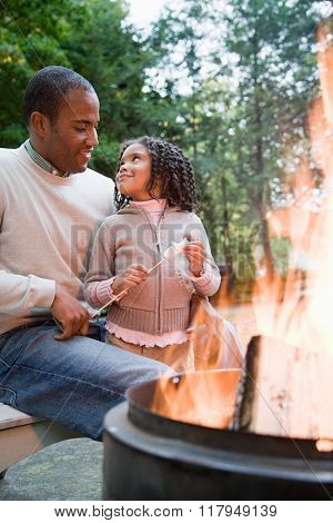 Father and daughter by fire