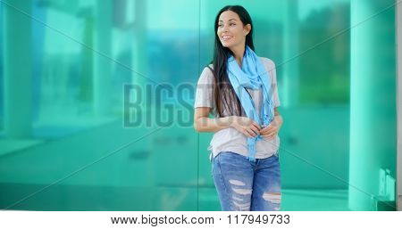 Happy woman looking sideways in front of glass