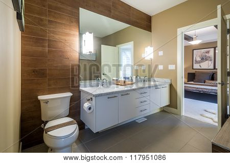 Interior design of a luxury bathroom with a wood wall and a large mirror overlooking a bedroom.