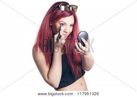 Woman Applyng Eyeliner Looking In A Pocket Mirror.