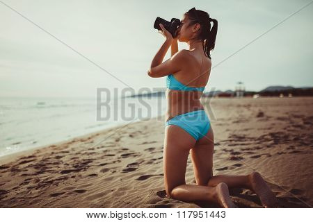 Happy woman photographer on vacation.Photographer taking sunset pictures with dslr camera and prime lens on the beach.Destination lifestyle photography.Summer memories.Capturing moment of life