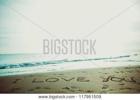 I love you sign written on sunset summer sand beach. Proposal on summer vacation. Romantic engagement. Vintage instagram filter