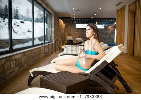 Body care and pampering in hotel luxury spa.Woman lying on the deckchair by swimming pool in resort.Wellness concept.Woman in bathrobe enjoying her time in hotel.Grain added