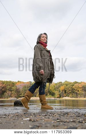 Woman walking near a lake and forest