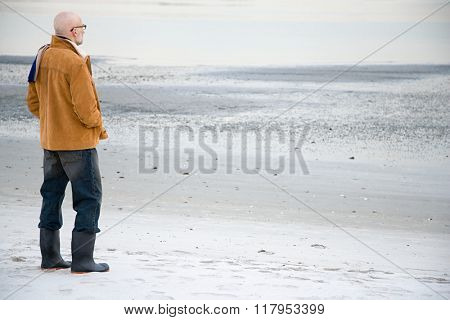 Mature man standing on an empty beach