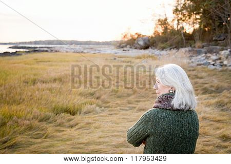 Woman standing on grass near the coast