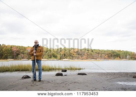Man standing near a lake and forest